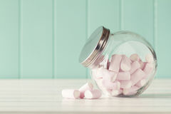 Marshmallows. Some marshmallows in a glass jar on a white wooden table with a robin egg blue background. Vintage Style royalty free stock photo