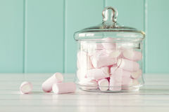 Marshmallows. Some marshmallow in a glass jar on a white wooden table with a robin egg blue background. Vintage Style stock photos