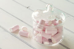 Marshmallows. Some marshmallow in a glass jar on a white wooden table. Vintage Style Royalty Free Stock Photos
