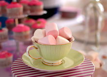 Marshmallows in a teacup. Pink and white marshmallows in a green teacup with pink cupcakes in the background Stock Photography