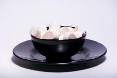 Marshmellow rose à l'intérieur de plat noir sur le fond blanc Photographie stock