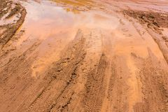 Marshy road. Wheel tracks on red color marshy road after raining Stock Photo