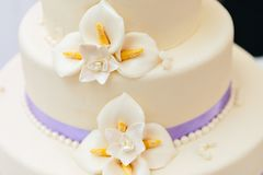 Marsipanblommor och purpurfärgat band på bröllopstårtan fotografering för bildbyråer