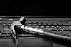 Marteau étendant l'ordinateur portable cassé par clavier Photos stock