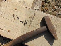Marteau avec des clous s'étendant sur la planche en bois images stock