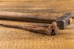 Marteau de cru avec des clous sur le fond en bois photos stock