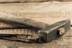 Marteau de cru avec des clous sur le fond en bois photo stock