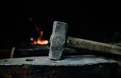 Marteau de forgeron sur l'enclume dans la perspective du feu Photographie stock libre de droits