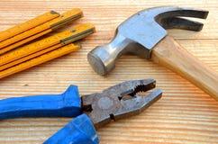 Marteau de griffe, mètre de charpentier et pinces Photos stock