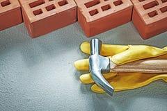 Marteau de griffe rouge de gants protecteurs de briques de construction sur le concret photos stock