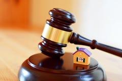 Marteau de juges sur le bloc sain à côté de la maison colorée jaune photographie stock libre de droits