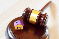 Marteau de juges sur le bloc sain à côté de la maison colorée jaune photos stock