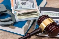Marteau de loi avec des dollars dans le livre et la menotte Image stock