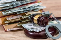 Marteau de loi avec des dollars dans le livre et des menottes Photographie stock