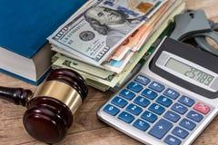 Marteau de loi avec des dollars dans le livre et des menottes Photo libre de droits