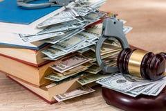 Marteau de loi avec des dollars dans le livre et des menottes Photos stock