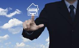 Marteau et clé de pressing d'homme d'affaires avec l'icône de maison au-dessus du bleu Photo libre de droits