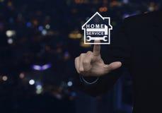 Marteau et clé de pressing d'homme d'affaires avec l'icône de maison au-dessus de la tache floue Image stock