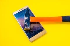 Marteau heurtant le téléphone intelligent sur le fond jaune image libre de droits