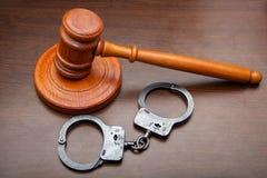 Marteau juridique de justice et menottes sur la table photo libre de droits