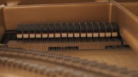 Marteaux en bois frappant sur des ficelles, jouant la musique de piano banque de vidéos