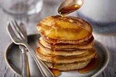 Martedì grasso, giorno di pancake I pancake hanno versato con miele sui precedenti dei piatti d'annata, delle forcelle e dei colt immagini stock