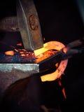 Martelant rougeoyer en acier - à il faut battre le fer quand il est chaud photo libre de droits