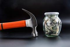 Martelez contre le pot complètement de dollars, économie d'argent photo stock