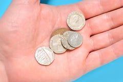 Martella le monete dei penny su una palma di una mano dell'uomo Fotografia Stock