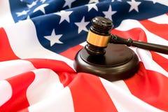 Martelletto di legno e tavola armonica del giudice che pongono sopra la bandiera degli Stati Uniti Martello e martelletto Legge e immagini stock