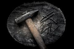 Martelli con la maniglia di legno con molte bullette per suole del ferro sul troncone di legno Stile maschio brutale Immagine Stock