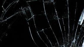 Martello che tagliato lastra di vetro contro il fondo nero video d archivio
