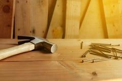 Martello, chiodo e legno e un mucchio di fondo di legno fotografia stock