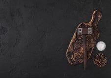 Martello d'annata della carne sul tagliere d'annata e sul fondo di pietra nero della tavola Utensili del macellaio Spazio per tes fotografie stock libere da diritti