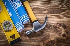 Martello da carpentiere blu del livello della costruzione dei disegni di ingegneria su legno Immagini Stock