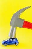 Martello da carpentiere d'acciaio con la maniglia rossa che colpisce sulla mini automobile blu sul YE Fotografia Stock