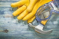 Martello da carpentiere dei guanti di cuoio dei vetri di protezione sul bordo di legno co Fotografia Stock Libera da Diritti