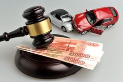 Martello del giudice con l'incidente di automobili del giocattolo e dei soldi su gray Fotografia Stock Libera da Diritti