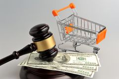 Martello del giudice, del carretto a mano e dei soldi su gray Immagine Stock