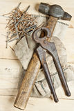 Martello dell'annata con i chiodi su priorità bassa di legno Fotografia Stock