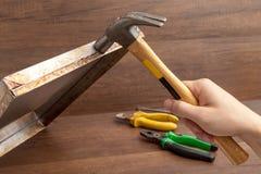 Martello della maniglia dell'uomo per colpire o riparare vassoio inossidabile su backgroud di legno Immagine Stock