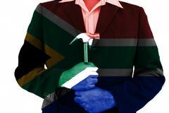Martello della tenuta dell'uomo di affari sulla bandiera della Sudafrica Fotografia Stock