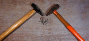 Martello e chiodi su un fondo di legno del bordo fotografia stock
