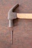 Martello e chiodi sul bordo di legno Fotografie Stock Libere da Diritti