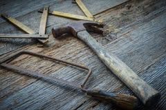 Martello, sega e nastro di misurazione su legno rustico Immagine Stock