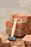 Martelo da protuberância que descansa contra parede de tijolo quebrada Fotografia de Stock Royalty Free
