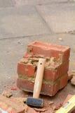 Martelo da protuberância que descansa contra parede de tijolo quebrada Imagem de Stock Royalty Free