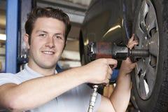 Martelo de ar de In Garage Using do mecânico na roda de carro imagem de stock royalty free