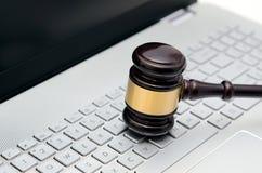 Martelo de madeira do juiz no teclado do branco do laptop Fotografia de Stock