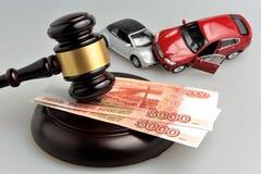 Martelo do juiz com acidente de carros do dinheiro e do brinquedo no cinza Fotografia de Stock Royalty Free